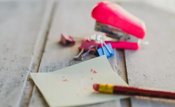 Paper, pencil shavings, and stapler on desk